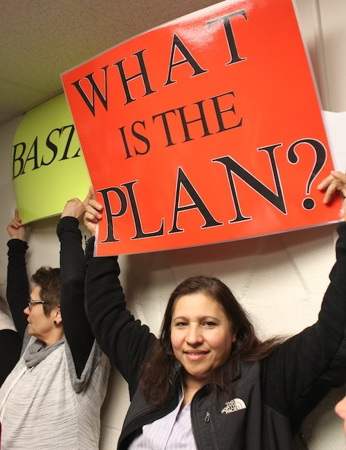 identity-advocacy-young-woman-holding-what-is-the-plan-sign