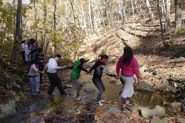 Identity Youth on a Retreat Crossing a Creek